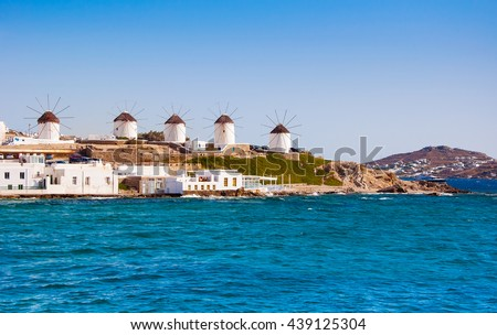 The famous windmills of Mykonos island surrounded by sea. - stock photo