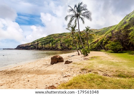 The far end of the beach at Hanauma Bay, Honolulu, Oahu, Hawaii. The Hanauma Bay Nature Preserve was established to restore a healthy ecosystem to the cove, an eroded flooded volcanic crater. - stock photo