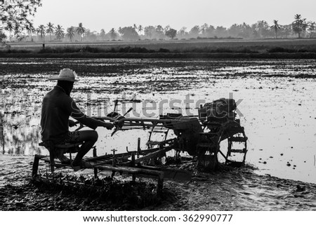 The farmers drive tractors on wet mud