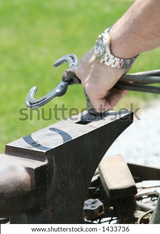 The farrier shapes the heated shoe using a hammer and anvil. Shallow dof.