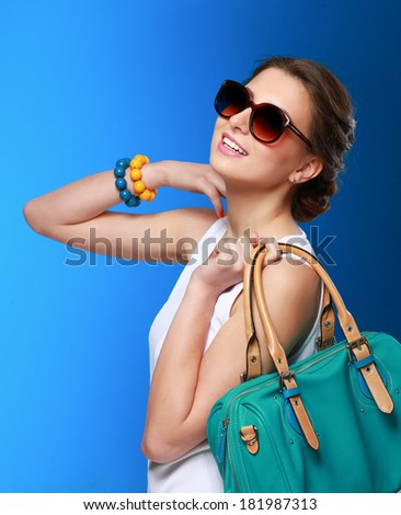 The fashionable young woman in sunglasses holding bag