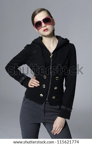The fashionable young woman in sunglasses standing