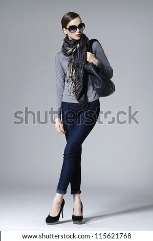 The fashionable young woman in sunglasses standing posing - stock photo