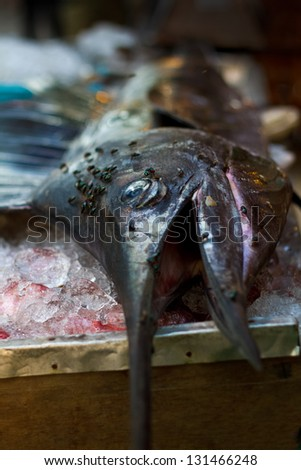 The fastest fish in the ocean lies on a table covered in flies and sold off in chunks for  a BBQ in Thailand. - stock photo