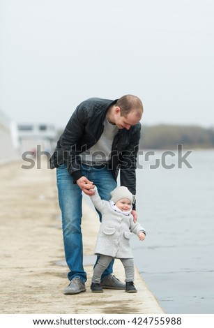 The father and the daughter walk. The father and the little daughter stand on the river embankment.
