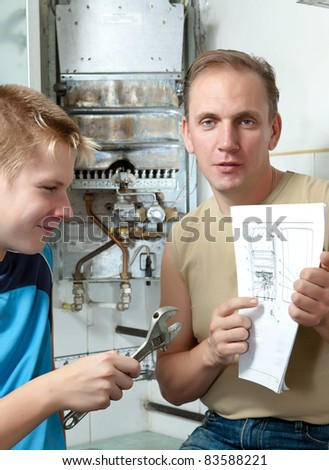 The father and the son-teenager together look the instruction on repair a gas water heater.