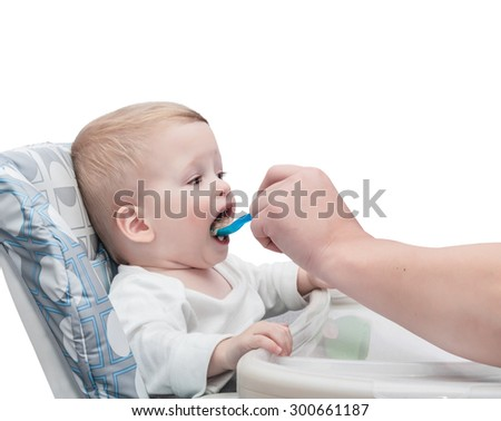 The father feeds with porridge of the one-year-old kid,  isolated on the white