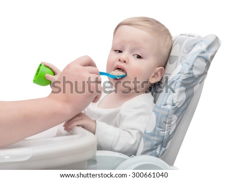 The father feeds with porridge of the one-year-old kid ,  isolated on white background - stock photo