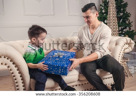 The father gives a gift to his son under the Christmas tree