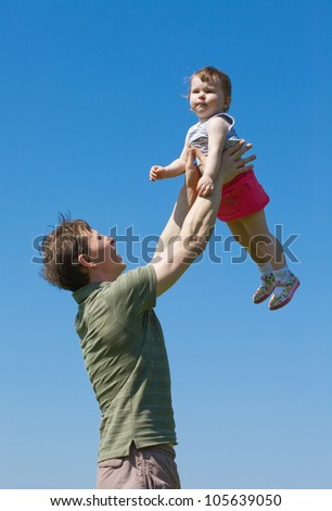The father holds the daughter on the hands lifted upwards. A happy family.