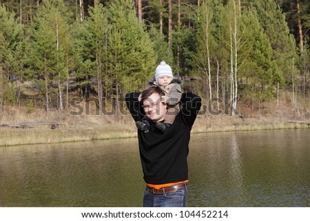 The father is holding his child on a lakeside in summer - stock photo