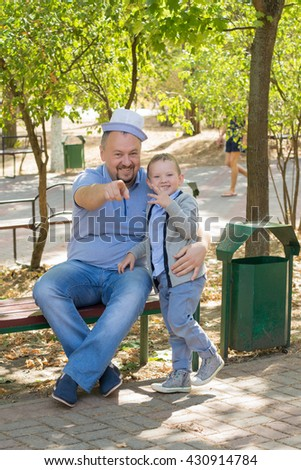 the father with the son sit in park on a bench and have fun - stock photo