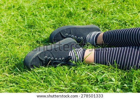 The feet and legs of a woman lying on the green grass