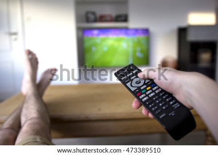The feet, legs and hand of a person watching TV, handling the remote. The feet are laying on a wooden table. A soccer match is visible on the TV in the background.