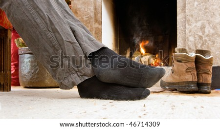 The feet of a hiker warming up by the fire - stock photo