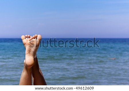 the feet of a relaxing girl lying at the beach.
