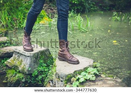 The feet of a young person trekking across stepping stones in a small pond - stock photo