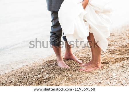 The feet of the bride and the groom playing on the beach. - stock photo