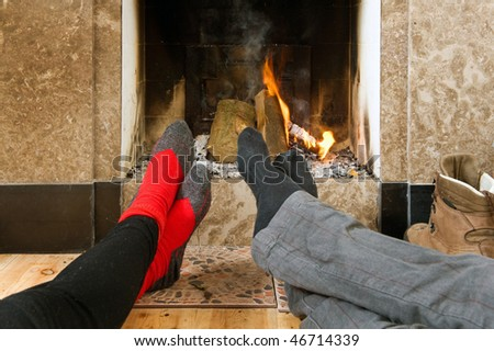The feet of two hikers warming up by the fire after a long hike on a winter's day - stock photo
