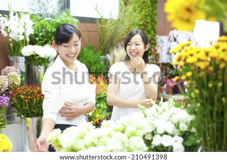 The female clerk in the flower shop and customers