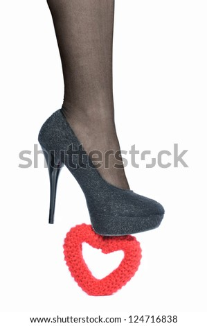 The female foot in black shoe presses  on knitted heart - stock photo