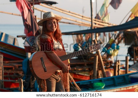 the female guitar player at the fishing village