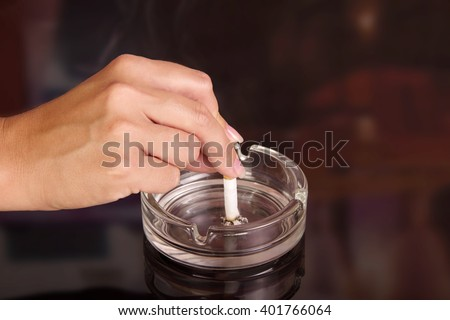 The female hand puts a cigarette in an ashtray on an abstract brown background. - stock photo
