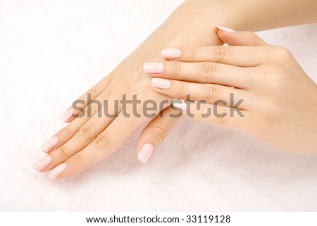 The female hand puts a cosmetic cream on other hand, isolated - stock photo