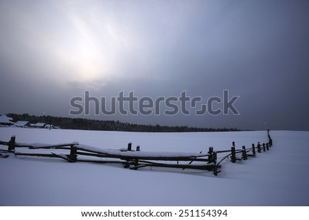 The fence of the village in a snowy forest. Russia