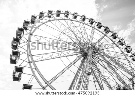 The Ferris wheel on the background of the cloudy sky