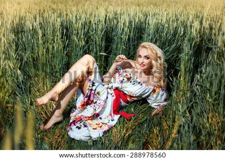 The field is a girl. The girl in beautiful summer dress with bare feet. - stock photo