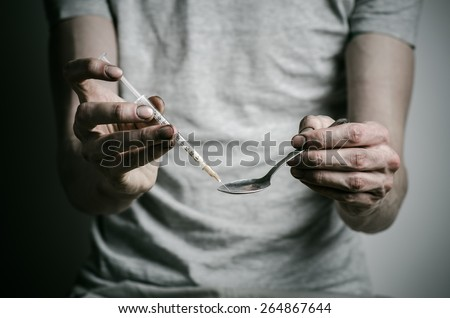 The fight against drugs and drug addiction topic: addict gaining a dirty syringe liquid drug from a spoon on a dark background - stock photo