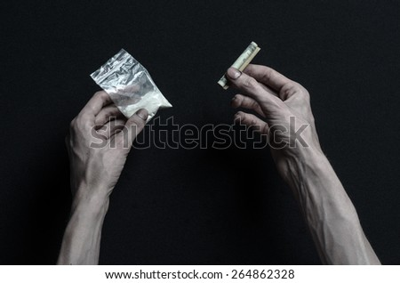 The fight against drugs and drug addiction topic: addict hand holding package of cocaine and wrapped dollar to sniff on a dark background in the studio