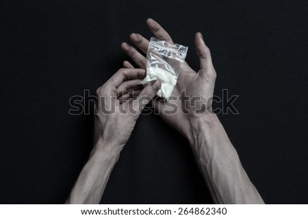 The fight against drugs and drug addiction topic: addict hand holding package of cocaine on a dark background in the studio top view - stock photo