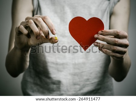 The fight against drugs and drug addiction topic: addict holding a narcotic pills and a red heart on a dark background
