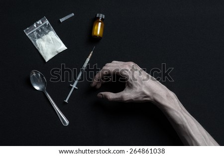 The fight against drugs and drug addiction topic: hand addict lies on a dark table and around it are drugs, a top studio - stock photo