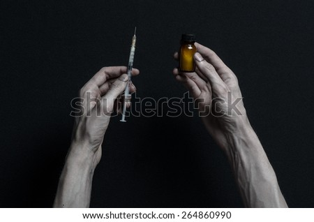 The fight against drugs and drug addiction topic: hand holding a syringe with a drug addict and a drug vial with the drug on a dark background in the studio - stock photo