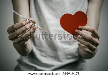 The fight against drugs and drug addiction topic: skinny dirty addict holding a syringe with a drug and red heart on a dark background - stock photo