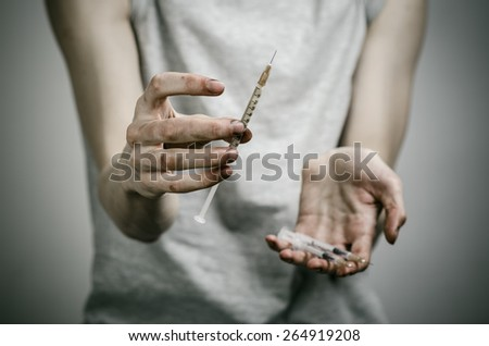 The fight against drugs and drug addiction topic: skinny dirty addict holding a syringe with a drug on a dark background