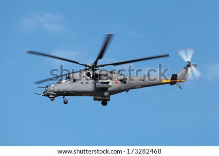 The fighting helicopter against the blue sky
