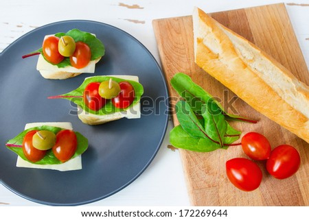 The fillet, tomatoes, salad on the board and mini sandwiches on the plate - stock photo
