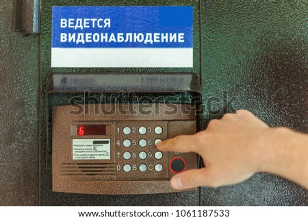The Finger Dials The Apartment Number On The Intercom. Text In Russian:  Ongoing Video