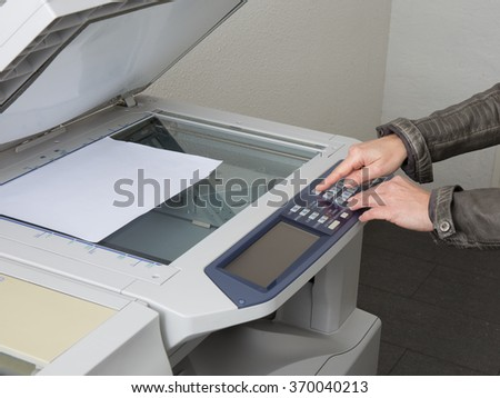 The finger is pressing the buttons of the copier at office