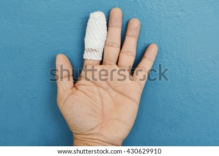 The finger must have wound with gauze bandage on blue background - stock photo