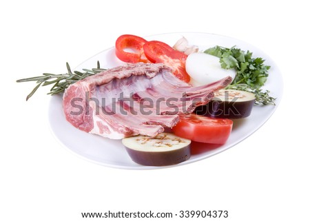 The finished dish of meat products with fresh vegetables on a white plate isolated on white background