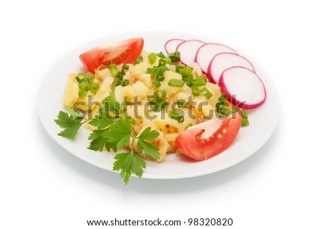 The finished meal from a fried potato with slices of a garden radish and tomato segments. It is strewed by green onions. - stock photo