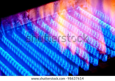The fire burns from a gas burner inside the boiler. - stock photo
