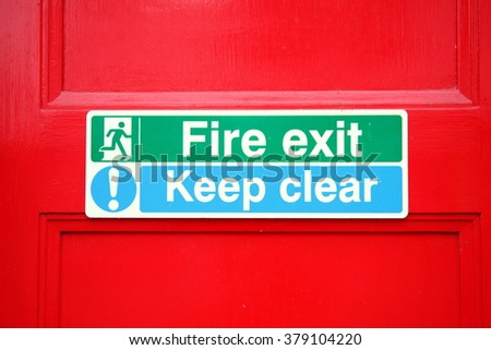 The fire exit signage scene on red color door represent the signage and concept related idea. - stock photo