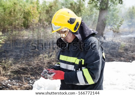 The firefighter battling with a fire on the car - stock photo