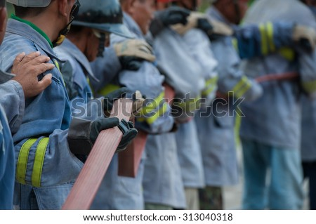 the firefighters hold the fire hose - stock photo
